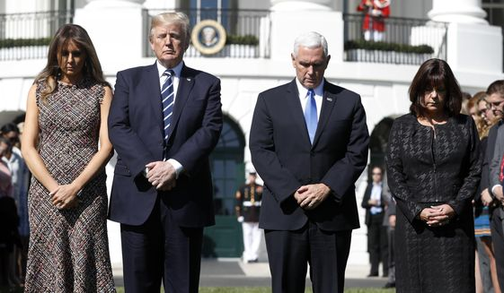 President Donald Trump and first lady Melania Trump stand with vice president Mike Pence and his wife Karen during a moment of silence to remember the victims of the mass shooting in Las Vegas, on the South Lawn of the White House in Washington, Monday, Oct. 2, 2017. (AP Photo/Pablo Martinez Monsivais)