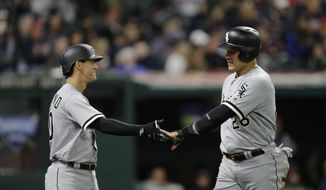 Chicago White Sox's Avisail Garcia, right, is congratulated by Tyler Saladino after scoring on a one-run double hit by Kevan Smith in the sixth inning of a baseball game against the Cleveland Indians, Saturday, Sept. 30, 2017, in Cleveland. (AP Photo/Tony Dejak)