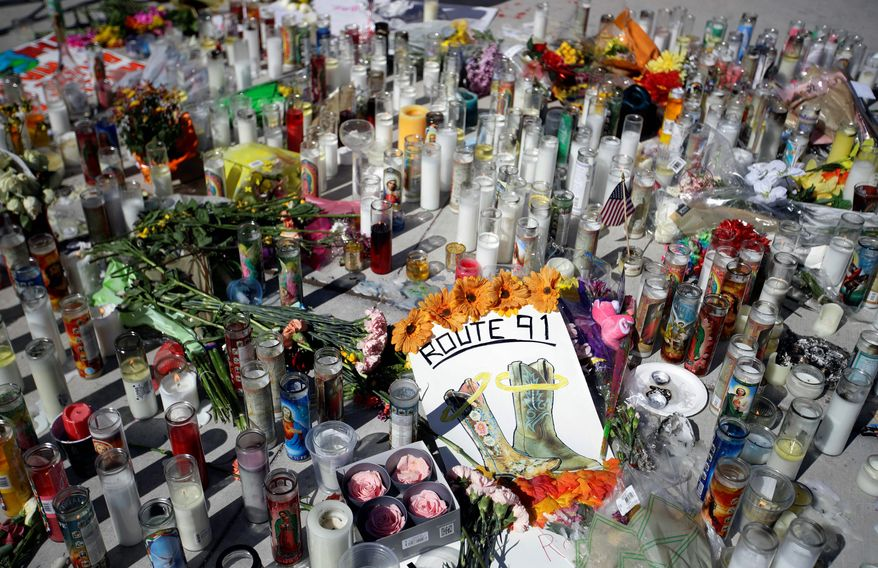 Flowers and candles are left at a makeshift memorial site on Las Vegas Boulevard on Tuesday, Oct. 3, 2017, in Las Vegas. A gunman opened fire on an outdoor music concert on Sunday killing dozens and injuring hundreds. (AP Photo/Chris Carlson)