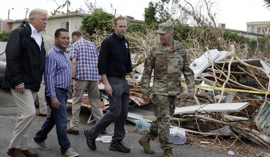 President Donald Trump takes a walking tour to survey hurricane damage and recovery efforts in a neighborhood in Guaynabo, Puerto Rico, Tuesday, Oct. 3, 2017. (AP Photo/Evan Vucci)