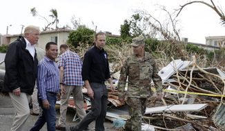 President Donald Trump takes a walking tour to survey hurricane damage and recovery efforts in a neighborhood in Guaynabo, Puerto Rico, Tuesday, Oct. 3, 2017. (AP Photo/Evan Vucci) **FILE**
