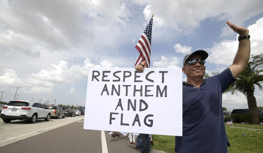Protesters upset with players kneeling during the national anthem stand along a road leading to Raymond James Stadium before an NFL football game between the Tampa Bay Buccaneers and the New York Giants Sunday, Oct. 1, 2017, in Tampa, Fla. (AP Photo/Phelan M. Ebenhack) ** FILE **