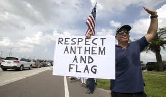 Protesters upset with players kneeling during the national anthem stand along a road leading to Raymond James Stadium before an NFL football game between the Tampa Bay Buccaneers and the New York Giants Sunday, Oct. 1, 2017, in Tampa, Fla. (AP Photo/Phelan M. Ebenhack)
