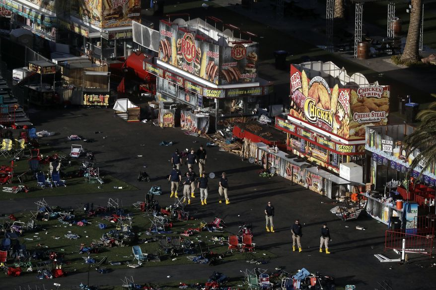Investigators work at a festival grounds across the street from the Mandalay Bay Resort and Casino on Tuesday, Oct. 3, 2017, in Las Vegas. Authorities said Stephen Craig Paddock broke windows on the casino and began firing with a cache of weapons, killing dozens and injuring hundreds at the music festival on Sunday. (AP Photo/Marcio Jose Sanchez)