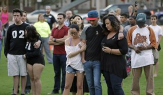 People embrace and bow their heads as nearby church bells ring during a vigil Tuesday, Oct. 3, 2017, in Orlando, Fla., to show solidarity with the victims of the shooting in Las Vegas.  Authorities said Stephen Craig Paddock broke windows on a Las Vegas casino and began firing with a cache of weapons Sunday, killing dozens and injuring hundreds at a country music festival. (AP Photo/John Raoux)