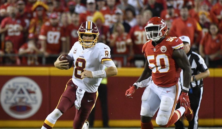 Washington Redskins quarterback Kirk Cousins (8) carries the ball between Kansas City Chiefs defensive back Terrance Mitchell (39) and linebacker Justin Houston (50) during the second half of an NFL football game in Kansas City, Mo., Monday, Oct. 2, 2017. The Kansas City Chiefs won 29-20. (AP Photo/Ed Zurga)