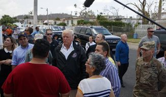 President Donald Trump talks with residents during a tour a neighborhood impacted by Hurricane Maria, Tuesday, Oct. 3, 2017, in Guaynabo, Puerto Rico. (AP Photo/Evan Vucci)