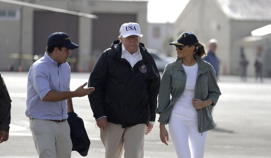 President Donald Trump and first lady Melania Trump walk with with Puerto Rico's Gov. Ricardo Rossello at the Luis Muniz Air National Guard Base before leaving the island in San Juan, Puerto Rico, Tuesday, Oct. 3, 2017. Trump is visiting Puerto Rico in the wake of Hurricane Maria.(AP Photo/Evan Vucci)