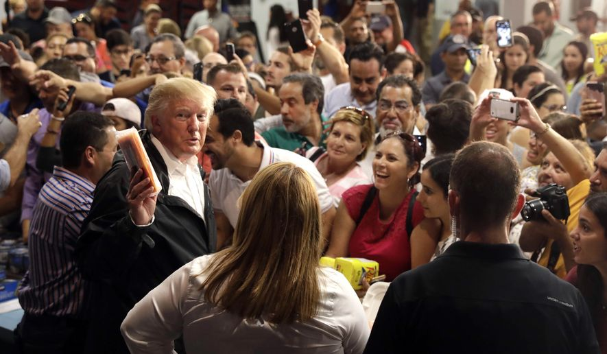 President Donald Trump hands out food to people effected by Hurricane Maria as he visits a disaster relief distribution center at Calgary Chapel in Guaynabo, Puerto Rico, Tuesday, Oct. 3, 2017. Trump is visiting Puerto Rico in the wake of Hurricane Maria.(AP Photo/Evan Vucci)
