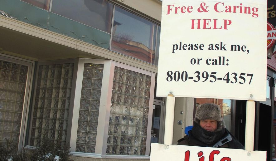 In this Feb. 20, 2013, file photo, an abortion protester stands outside the Red River Valley Women's Clinic in Fargo, N.D., the state's lone abortion facility. (AP Photo/Dave Kolpack, File)