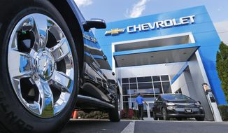 This Wednesday, April 26, 2017, photo shows the logo on the wheel of an SUV in front of a Chevrolet dealership in Richmond, Va. General Motors and Ford each posted strong U.S. sales in September 2017, confirming predictions that the industry could rebound for the month. (AP Photo/Steve Helber)