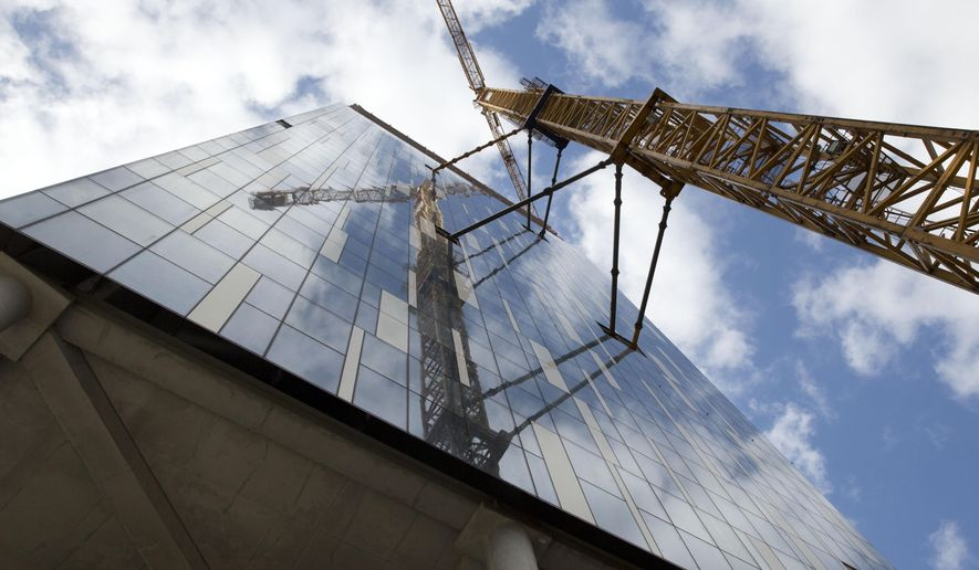 A crane looms over the facade of a building which is proposed to host the European Medicines Agency during a presentation of Belgium's bid to host the agency in Brussels, Tuesday, Oct. 3, 2017.  There is heavy competition to relocate the European Medicines Agency and the European Banking Authority from London to be headquartered in an EU country, with many EU nations still confident they can win their bid which will bring money and prestige to the host country.  (AP Photo/Virginia Mayo)