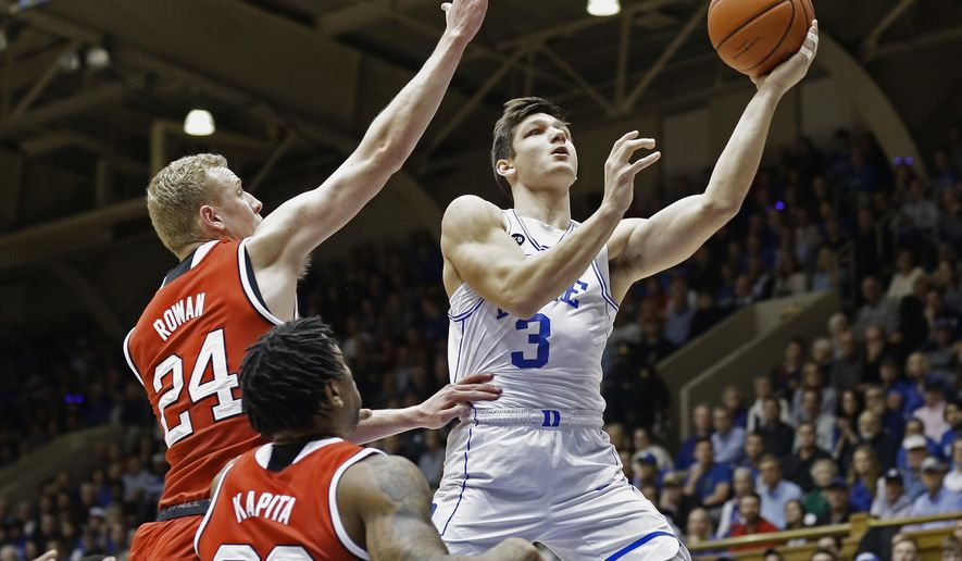 FILE - In this photo taken Jan. 23, 2017, file photo,  Duke's Grayson Allen (3) drives to the basket as North Carolina State's Maverick Rowan (24) and Ted Kapita (23) defend during the first half of an NCAA college basketball game in Durham, N.C. A series of tripping incidents had fans and enemies scrutinizing every move made by the polarizing guard, and led to the embarrassing loss of his team captaincy. He's back for his senior year, back in a leadership position and eager to prove he's not the villain he's been made out to be. (AP Photo/Gerry Broome, File)