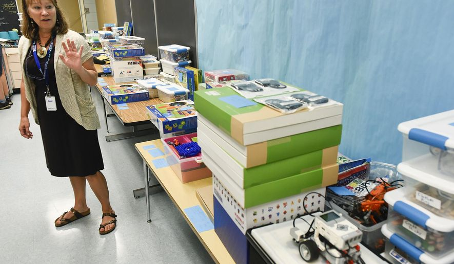 In this Thursday, Sept. 14, 2017 photo, Jenny McNew, media specialist, show the STEM project boxes for different grades at Talahi Community School in St. Cloud, Minn. (Jason Wachter/St. Cloud Times via AP)