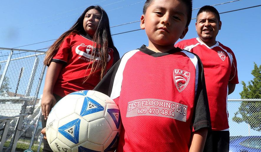 In this Saturday, Sept. 16, 2017, photo, Gregorio Huestipa, 35, his 15-year-old daughter, Stephanie, and son, Brain, 4, of Pleasantville, N.J., pose for a photo as they get ready to play a community soccer game. Huestipa is dealing with a threat of immigration deportation ICE arrested Gregorio over the summer for living here illegally and held him in jail in Newark for more than a month. (Edward Lea/The Press of Atlantic City via AP)
