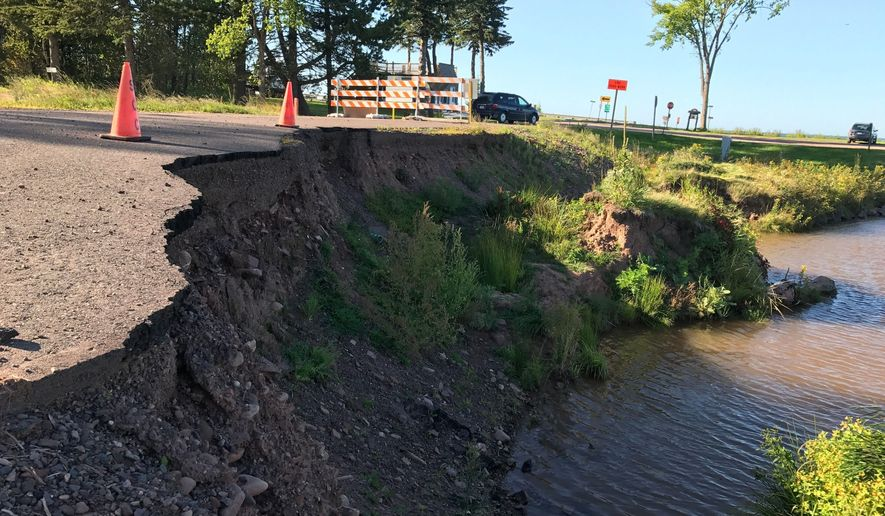 It has been 14 months since the night of the Saxon Harbor flood, and they're still waiting to rebuild. Iron County A, the two-lane blacktop road that winds around the hills to Lake Superior from Highway 122, is still washed out; crews built a temporary bridge and gravel lane on the road to allow cars to reach a shoreline parking lot, boat ramp and a few nearby homes.  (Keith Uhlig//The Wausau Daily Herald via AP)