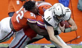 FILE - In this Saturday, Sept. 30, 2017, file photo, Vanderbilt quarterback Kyle Shurmur (14) is sacked by Florida defensive lineman Jabari Zuniga, left, and defensive lineman Jachai Polite during the first half of an NCAA college football game in Gainesville, Fla. Vanderbilt coach Derek Mason challenging his offensive line to play better hasn't helped the Commodores run the ball better, and now they host No. 5 Georgia. (AP Photo/John Raoux, File)