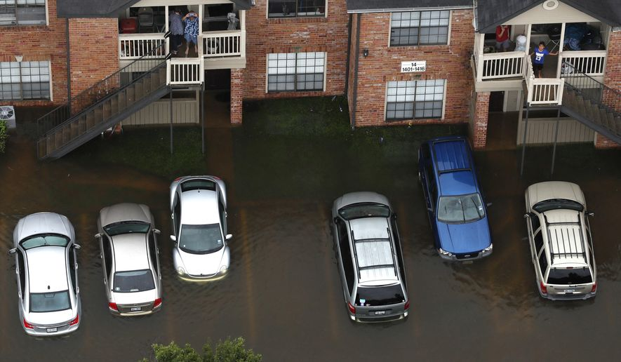 FILE - In this Aug. 29, 2017, aerial photo, floodwaters from Tropical Storm Harvey surround an apartment complex in Houston. The same technology that connected students and teachers in the aftermath of hurricanes Harvey and Irma is easing their transition back to class. That technology includes smartphone exchanges, social media, messaging apps and websites. (Brett Coomer/Houston Chronicle via AP, File)