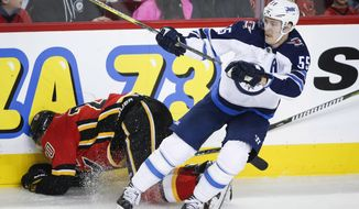 Winnipeg Jets' Mark Scheifele, right, checks Calgary Flames' Curtis Lazar during first-period NHL preseason hockey game action in Calgary, Alberta, Saturday, Sept. 30, 2017. (Jeff McIntosh/The Canadian Press via AP)