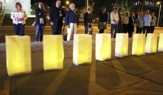 Luminaries for victims of the the Sunday evening shooting tragedy in Las Vegas are lit on the front steps of Greene Memorial United Methodist Church surrounded by those brought together in prayer and solidarity on Monday, Oct. 2, 2017, in Roanoke, Va. (Heather Rousseau/The Roanoke Times via AP)
