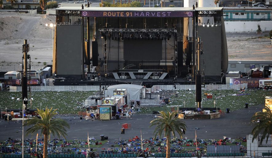 Debris litters a festival grounds across the street from the Mandalay Bay resort and casino Tuesday, Oct. 3, 2017, in Las Vegas. Authorities said Stephen Craig Paddock broke windows on the casino and began firing with a cache of weapons, killing dozens and injuring hundreds at a music festival at the grounds. (AP Photo/John Locher)