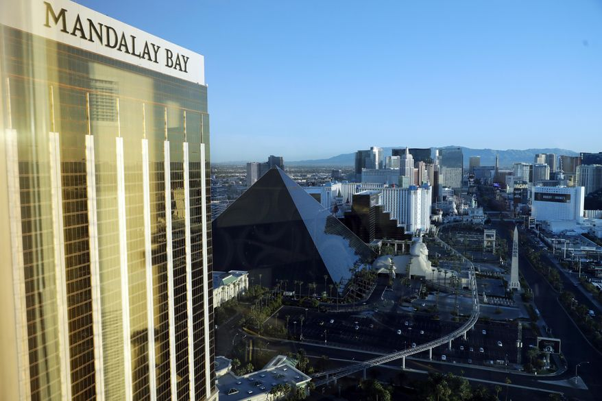The Mandalay Bay Resort and Casino, at left, stands across the street from a festival grounds Tuesday, Oct. 3, 2017, in Las Vegas. Authorities said Stephen Craig Paddock broke windows on a high floor of the hotel and began firing with a cache of weapons, killing dozens and injuring hundreds at a music festival at the grounds. (AP Photo/Marcio Jose Sanchez)