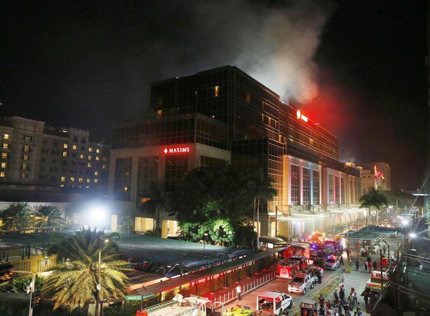 In this Friday, June 2, 2017, photo, smoke rises from an attack inside the Resorts World Manila complex in suburban Pasay city, southeast of Manila, Philippines. Around the globe, risks of terrorism and other violence have made tight security at hotels and resorts routine. The most recent major attack in Asia, at the Resorts World Manila casino in the Philippines, shares similarities with the shooting Sunday night in Las Vegas that killed 59 and injured more than 500 people. (AP Photo/Bullit Marquez, File)