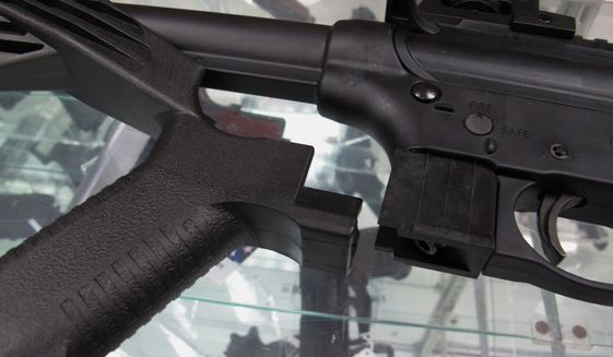 "A ""bump"" stock is displayed next to a disassembled .22-caliber rifle at North Raleigh Guns in Raleigh, North Carolina, Feb. 1, 2013. (AP Photo/Allen Breed) ** FILE **"