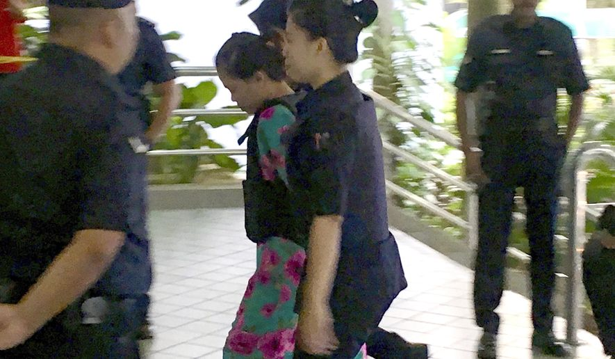 Indonesian Siti Aisyah, center, escorted by police as she arrived for court hearing at Shah Alam court house in Shah Alam, Malaysia, Tuesday, Oct. 3, 2017. Two women accused of smearing a banned nerve agent on the face of the estranged half brother of North Korea's leader pleaded not guilty as their trial began Monday in the Feb. 13 assassination at a crowded Malaysian airport terminal.(AP Photo/Vincent Thian)