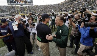 FILE - In this Oct. 29, 2016, file photo, Michigan head coach Jim Harbaugh, left, greets Michigan State head coach Mark Dantonio after the Wolverines won 32-23 in an NCAA college football game in East Lansing, Mich. It's the biggest week of the year for Michigan State and Michigan. This year, the game comes early in the conference season, and it'll be under the lights in Ann Arbor. (AP Photo/Carlos Osorio, File)