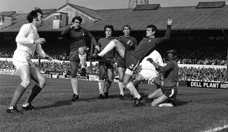 FILE - In this Oct. 18, 1969 file photo, Chelsea's Eddie McCreadie, second right, kicks clear from scrimmage in front West Bromwich's Jeff Astle, left, during the English League Division one soccer match between Chelsea and West Bromwich Albion at Stamford Bridge Stadium in London. The family of former England striker Jeff Astle, whose death at age 59 in 2002 was attributed to repeatedly heading heavy, leather balls, has been pushing for better protection for modern players. (AP Photo/Robert Rider, file)