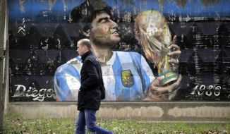 A man walks past a fence with graffiti depicting Argentina's soccer legend Diego Maradona in the town of Volkhov, 130 km (80 miles) east of St.Petersburg, Russia, Monday, Oct. 2, 2017. (AP Photo/Dmitri Lovetsky)