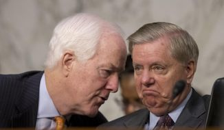 Senate Majority Whip Sen. John Cornyn, R-Texas., left, speaks with Sen. Lindsey Graham, R-S.C., right, during a Senate Judiciary Committee hearing on Capitol Hill in Washington, Tuesday, Oct. 3, 2017, on the Trump Administration's decision to end Deferred Action for Childhood Arrivals otherwise known as DACA. (AP Photo/Andrew Harnik)