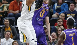 Utah Jazz center Rudy Gobert, left, dunks on Sydney Kings center Isaac Humphries (0) during the first half of a preseason NBA basketball game Monday, Oct. 2, 2017, in Salt Lake City. (AP Photo/Rick Bowmer)