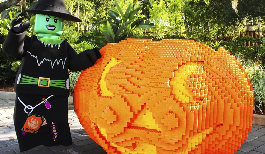This 2015 image shows a giant pumpkin made from Legos at Legoland in Winter Haven, Fla., with a costumed greeter standing nearby. The costumed witch and giant Lego pumpkin are also part of the 2017 Brick or Treat event at Legoland. (Legoland Florida Resort via AP)