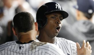 New York Yankees' Didi Gregorius, right, celebrates with Gary Sanchez after hitting a three-run home run during the first inning of the American League wild-card playoff baseball game against the Minnesota Twins in New York, Tuesday, Oct. 3, 2017. (AP Photo/Kathy Willens)