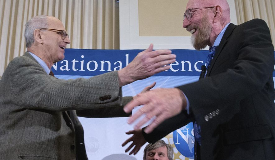 FILE - In this Feb. 11, 2016 file photo, Laser Interferometer Gravitational-Wave Observatory (LIGO) Co-Founder Rainer Weiss, left, and Kip Thorne, right, hug on stage accompanied by Interferometer Gravitational-Wave Observatory (LIGO) Exectutive Director David Reitze, bottom, during a news conference at the National Press Club in Washington, USA. The Nobel Physics Prize 2017 is announced Monday Oct. 3, 2017, is awarded to three scientists Rainer Weiss of the Massachusetts Institute of Technology, and Barry Barish and Kip Thorne of the California Institute of Technology. (AP Photo/Andrew Harnik, File)