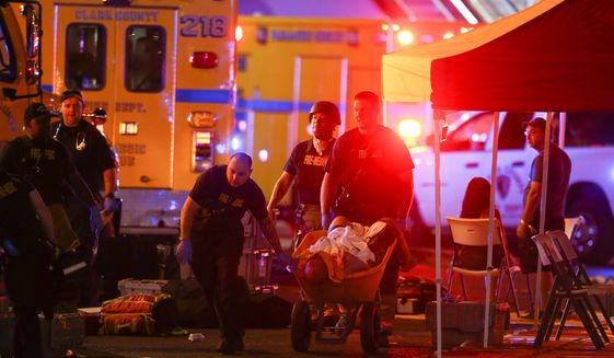 A wounded person is walked in on a wheelbarrow as Las Vegas police respond during an active shooter situation on the Las Vegas Strip in Las Vegas Sunday, Oct. 1, 2017. Multiple victims were being transported to hospitals after a shooting late Sunday at a music festival on the Las Vegas Strip. Photo by Chase Stevens/Las Vegas Review-Journal via Associated Press