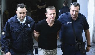 Police officers escorted Alexander Vinnik from a courthouse on Wednesday after a Greek court ruled for extradition to the United States, where he is wanted in connection with a $4 billion bitcoin fraud case. (Associated Press)