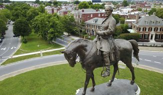 This Tuesday June 27, 2017, file photo shows the statue of Confederate General Robert E. Lee that stands in the middle of a traffic circle on Monument Avenue in Richmond, Va.  (AP Photo/Steve Helber, File) **FILE**