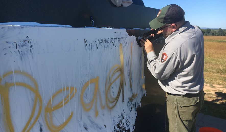 A National Park Service ranger inspects a Civil War era monument to Stonewall Jackson, which was vandalized over night with white and gold paint. (National Park Service)