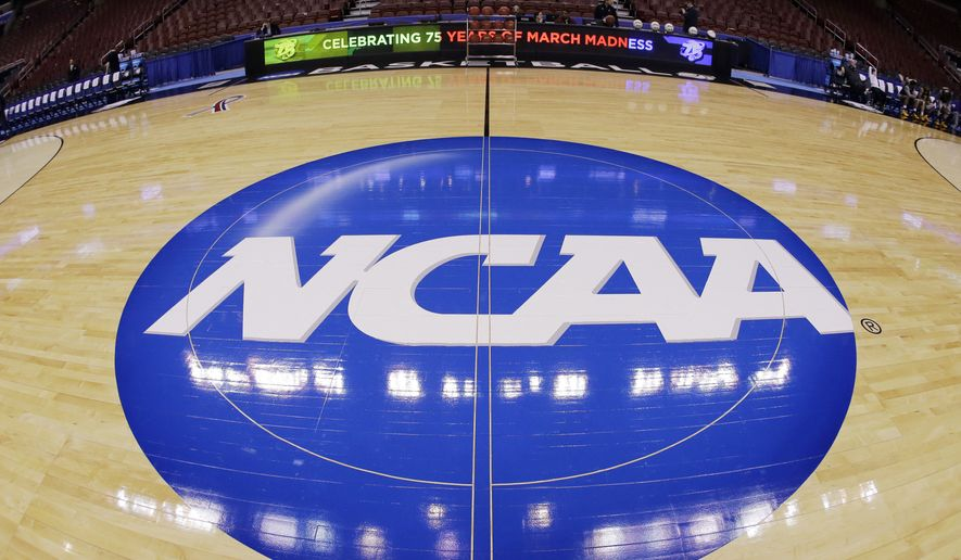 FILE - In this March 21, 2013, file photo, taken with a fisheye lens, the NCAA logo is displayed at mid-court before Albany's practice for a second-round game of the NCAA college basketball tournament in Philadelphia. An NCAA committee is developing a proposal that would eliminate a school's ability to essentially block an athlete from transferring. The NCAA said Wednesday, Oct. 4, 2017, that the Division I Council could introduce legislation to reform transfer rules as early as January. The Division I Transfer Working Group met this week and considered feedback from more than 2,000 administrators, coaches and faculty members. (AP Photo/Matt Slocum, File) **FILE**