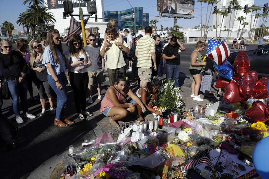 People light candles at a memorial for victims of the mass shooting Wednesday, Oct. 4, 2017, in Las Vegas. A gunman opened fire on an outdoor music concert on Sunday. It was the deadliest mass shooting in modern U.S. history, with dozens killed and hundreds injured, some by gunfire, some during the chaotic escape. (AP Photo/Marcio Jose Sanchez)
