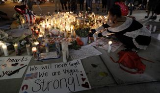 A woman places a candle at a memorial for victims of the mass shooting Tuesday, Oct. 3, 2017, in Las Vegas. A gunman opened fire on an outdoor music concert on Sunday. It was the deadliest mass shooting in modern U.S. history, with dozens killed and hundreds injured, some by gunfire, some during the chaotic escape. (AP Photo/Marcio Jose Sanchez)