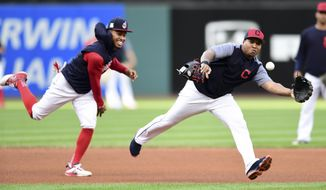Cleveland Indians' Jose Ramirez, right, fields a ball chased by Francisco Lindor during a team workout, Wednesday, Oct. 4, 2017, in Cleveland. The Indians will play the New York Yankees in Game 1 of the ALDS on Thursday. (AP Photo/David Dermer)