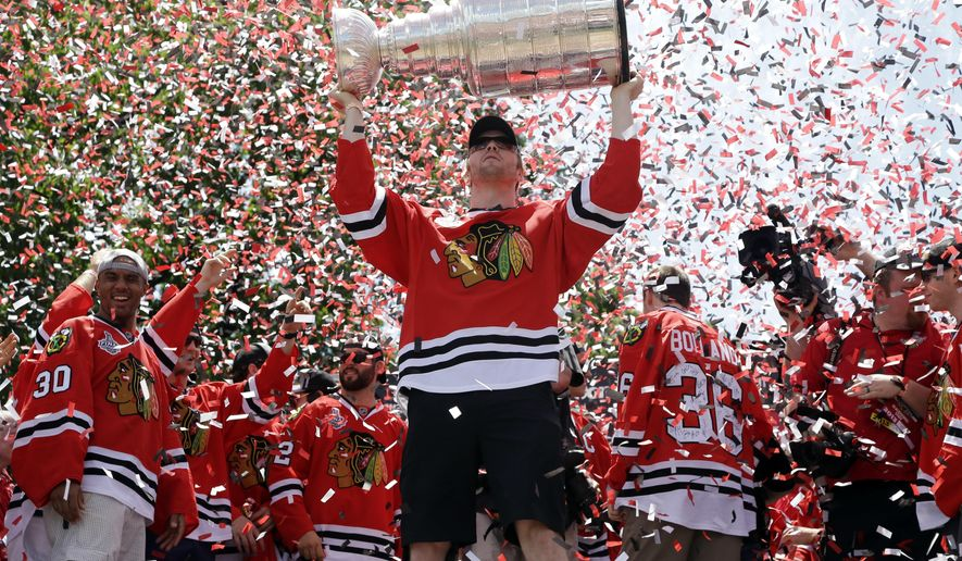 FILE - In this June 28, 2013, file photo, Chicago Blackhawks left wing Bryan Bickell (29) holds up the Stanley Cup Trophy during a rally in Grant Park for the NHL Stanley Cup hockey champions, in Chicago. Bickell has signed a one-day contract so he can retire with the Blackhawks. Bickell was selected by Chicago in the second round of the 2004 draft and spent his first nine seasons with the Blackhawks, winning three Stanley Cup championships. He was traded to Carolina in June 2016. The 31-year-old Bickell was diagnosed with multiple sclerosis last November and played in just 11 games with the Hurricanes. (AP Photo/Nam Y. Huh, File)