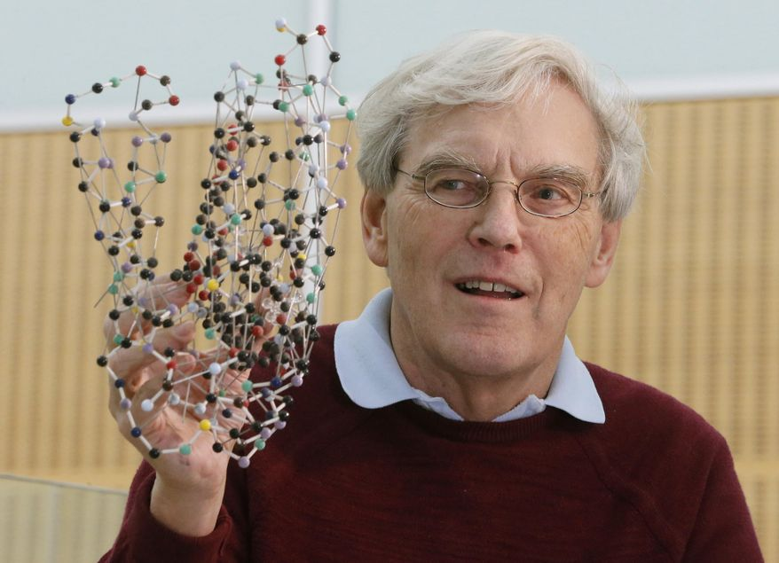 Richard Henderson, one of the 2017 Nobel Prize winners in Chemistry, holds a bacterio rhodopsin model prior to a press conference at the Laboratory of Molecular Biology in Cambridge, England, Wednesday, Oct. 4, 2017. Three researchers based in the U.S., U.K. and Switzerland won the Nobel Prize in Chemistry on Wednesday for developments in electron microscopy. The 9-million-kronor ($1.1 million) prize is shared by Jacques Dubochet of the University of Lausanne, Joachim Frank at New York's Columbia University and Richard Henderson of MRC Laboratory of Molecular Biology in Cambridge, Britain. (AP Photo/Frank Augstein)