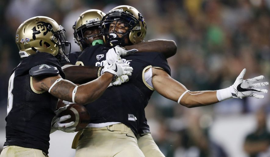 FILE - In this Friday, Sept. 1, 2017, file photo, Colorado defensive back Evan Worthington, front right, is congratulated by defensive backs Afolabi Laguda, back right, and Trey Udoffia, left, after making an interception in the second half of an NCAA college football game against Colorado State in Denver. Worthington is making the most of his second chance on Colorado's roster after being suspended for violating team rules last year. (AP Photo/David Zalubowski, File)