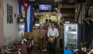 A waitress at a private restaurant waits for customers in Havana, Cuba, Tuesday, Oct. 3, 2017. Thousands of private Cuban businesses have invested heavily in private homes, cars and restaurants, hoping to cash in on an expected wave of American travelers to the island. Now that the U.S. State Department has issued a travel warning for the country, their investments are at risk.(AP Photo/Desmond Boylan)