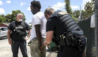 In a Thursday, July 27, 2017 photo, Deputy U.S. Marshall Leslie Ramin, left, talks with a suspect as he is handcuffed by Houston Police Officer Cole Smith in Houston. The suspect surrendered peacefully after his brother flagged down the officers as they searched nearby. ( Jon Shapley/Houston Chronicle via AP)/Houston Chronicle via AP)
